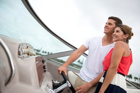 Romantic couple driving a boat and looking happy