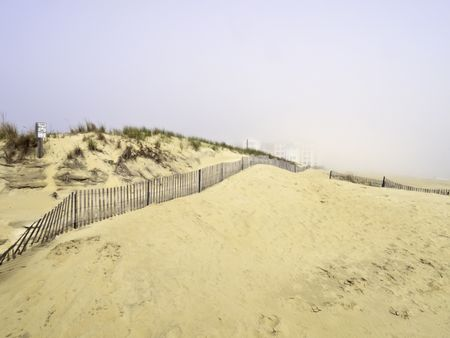 Coastal mirage: High-rises beyond sand dunes partially obscured by morning fog moving in from the Atlantic Ocean south of Virginia Beach, Virginia
