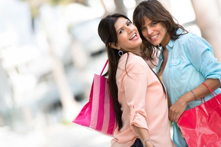 Happy shopping girls holding bags and smiling