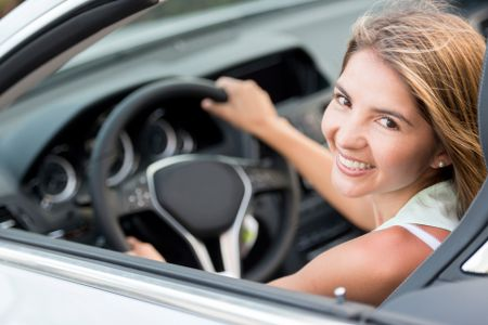 Female driver in a car looking very happy