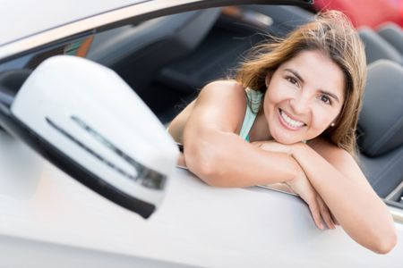Woman in a convertible car looking very happy