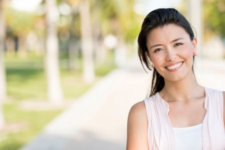 Portrait of a happy woman smiling at the park