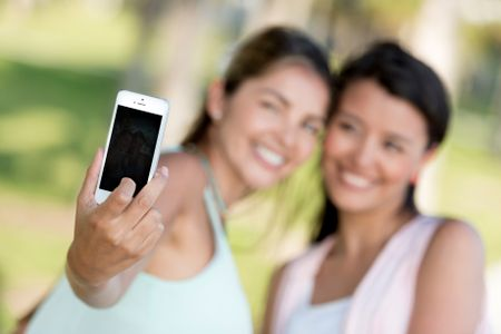 Girls taking a picture of themselves with the mobile phone