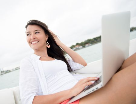 Woman social networking on a boat from laptop computer
