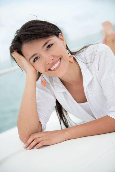 Beautiful summer woman lying on a boat enjoying her holidays