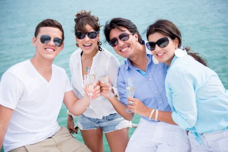 Group of friends enjoying the summer drinking champagne and sailing