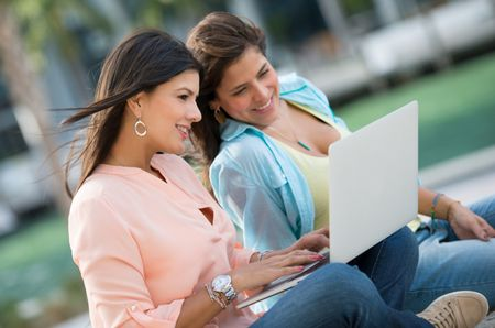 Female friends using a laptop at the park and smiling