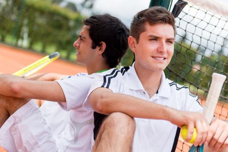Male tennis players sitting at the court