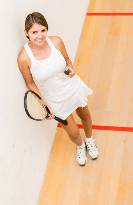 Female player of squash holding racket and ball