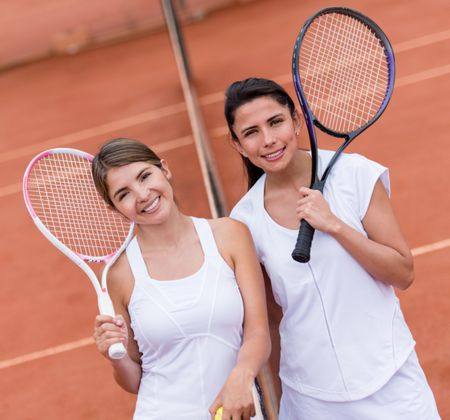 Female tennis players looking happy at a clay court