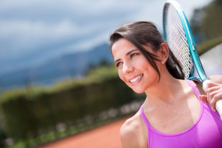 Female tennis player holding a racket outdoors