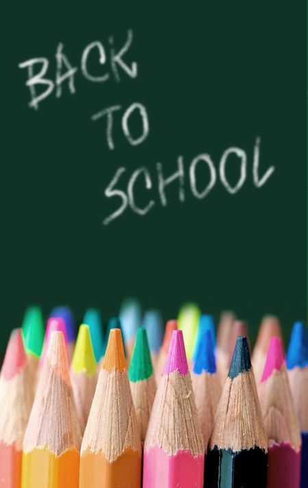 back to school - colour pencils in vibrant tones in front of a blackboard in a classroom