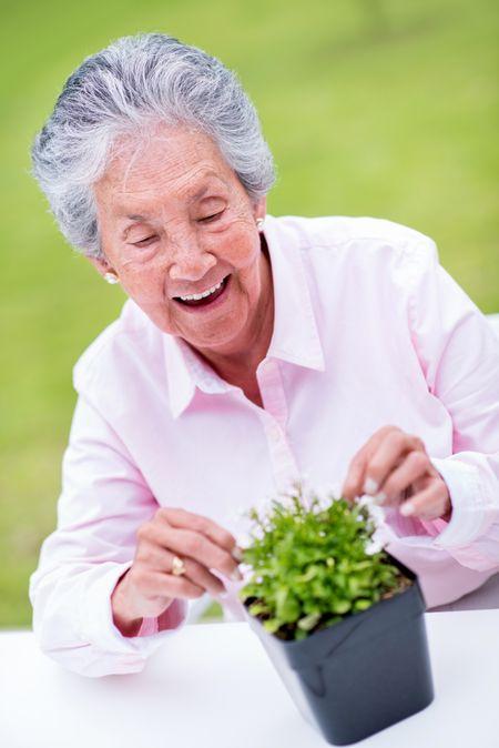 Beautiful senior woman gardening outdoors looking very happy