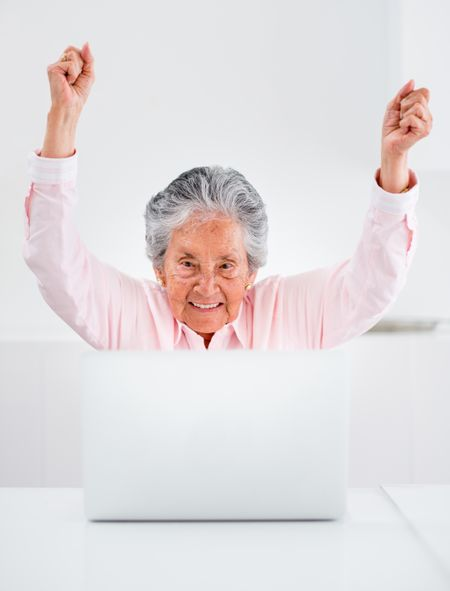 Happy elder woman with a laptop and arms up