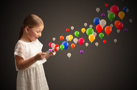 Cute little girl using tablet with colourful balloons concept