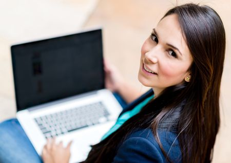 Casual woman working on a laptop computer and smiling