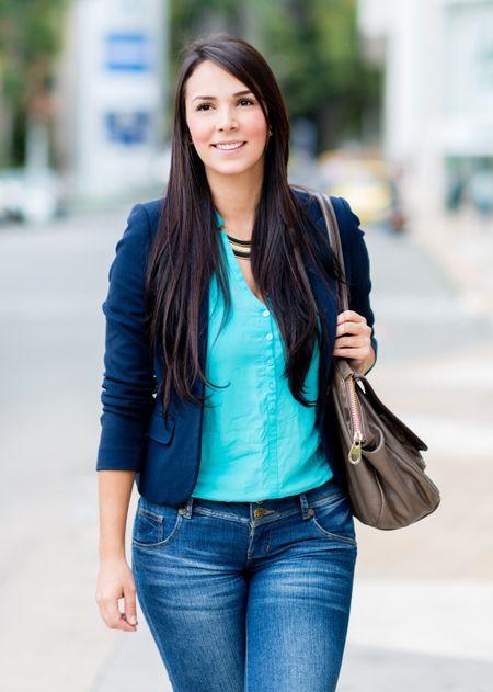 Beautiful casual woman walking outdoors holding her purse
