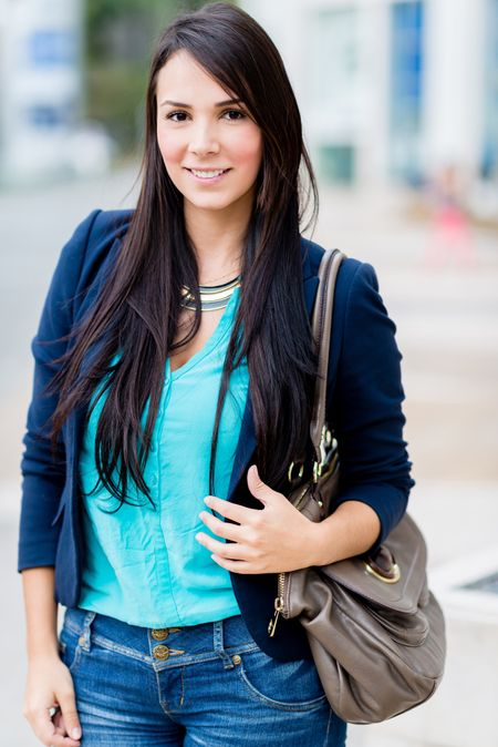 Beautiful casual woman on the street holding her purse
