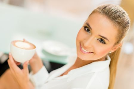 Beautiful woman drinking a cup of coffee and smiling