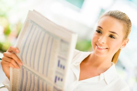 Woman reading the newspaper and looking very happy