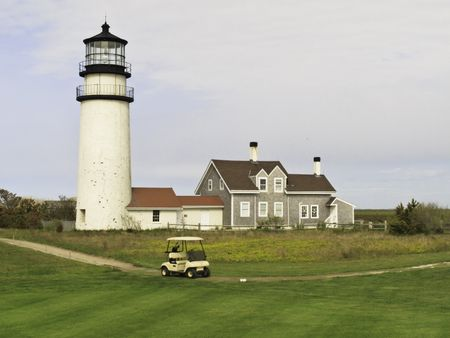 Golf cart on path around putting green by historic lighthouse and station in Cape Cod