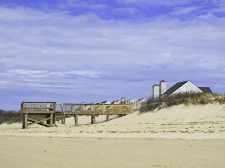 Coastal landscape: Beach view of boardwalk and deck by dune near peaked roofs of houses in Cape Cod, Massachusetts