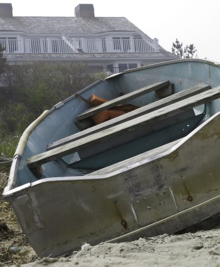 Vacant rowboat beached near house in Cape Cod on misty afternoon (selective focus)