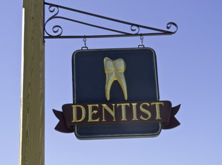 Dentist's sign with gold tooth against a blue sky