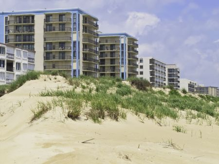 Coastal landscape: Row of high-rises with ocean views by dune along beach in Ocean City, Maryland