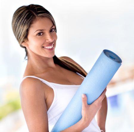 Beautiful portrait of a woman holding yoga mat