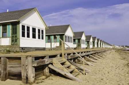 Conformity at the beach: Long row of identical white beach cottages in Cape Cod, Massachusetts