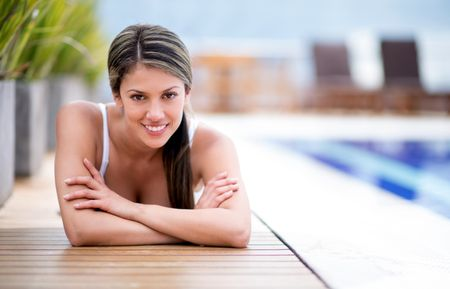 Beautiful woman lying by the pool and smiling