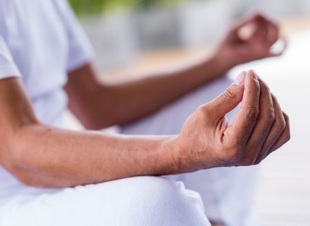Yoga man meditating and making a zen symbol with his hand