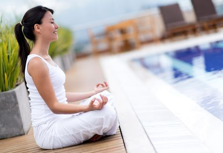 Yoga woman meditating by the pool looking very relaxed