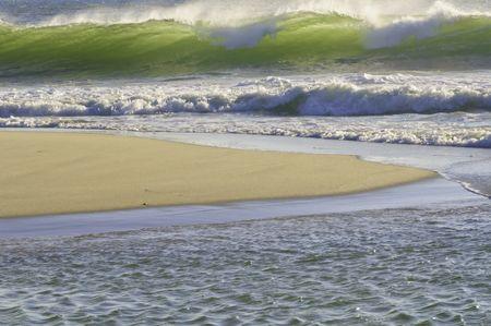 Translucent wave breaking green toward sandy beach in the morning, Cape Cod, Massachusetts