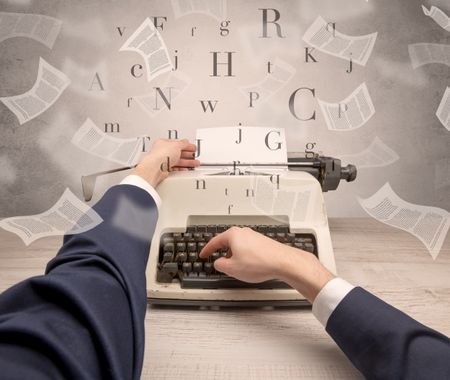 First person perspective hand typewriting with flying documents around