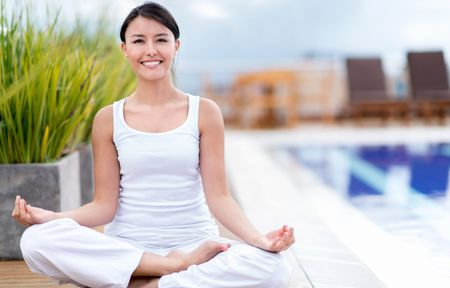 Happy woman doing yoga outdoors and smiling