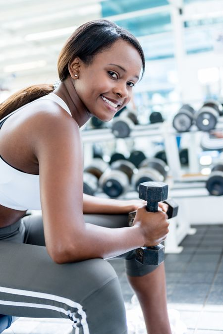 Gym woman exercising with free weights and smiling