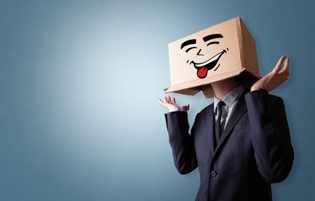 Young boy standing and gesturing with a cardboard box on his head
