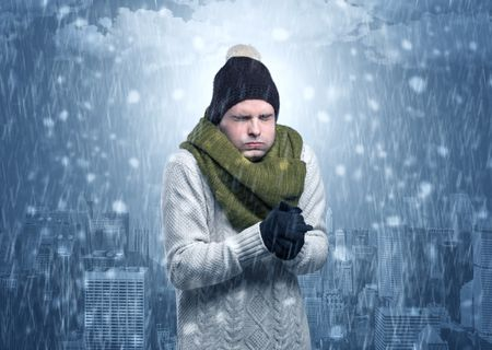 Young man freezing in warm clothing with city concept