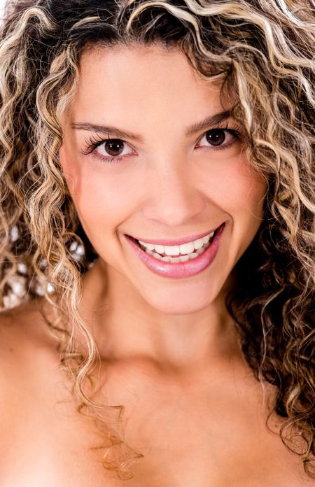 Female beauty portrait of a woman smiling with curly hair