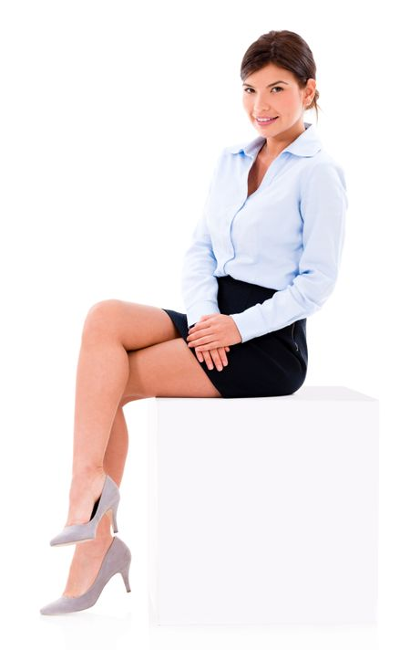 Beautiful business woman sitting on a cube - isolated over white background