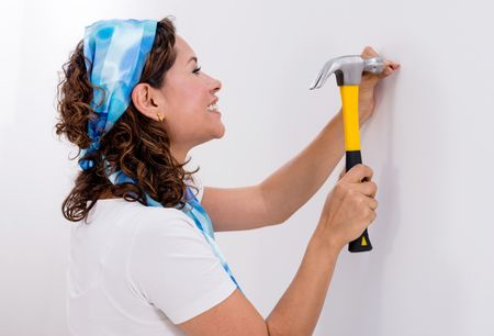 Casual woman hitting a nail in a wall with a hammer