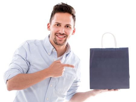 Happy shopping man pointing at a bag - isolated over white
