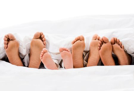 Family in bed with their feet out  - isolated over white