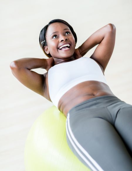 Happy woman at the gym exercising with a Pilates ball