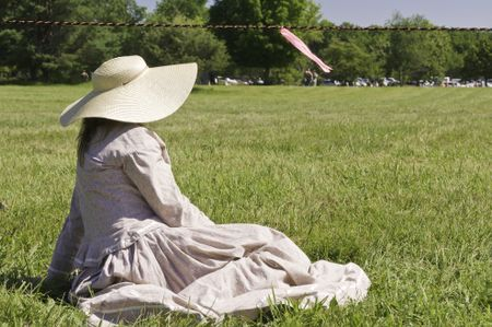 Unidentified woman actor in sun hat and period dress sits waiting by roped-off battlefield during reenactment of battle in the American Civil War (1861-1865)