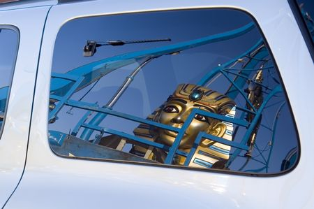 Reflection of huge sphinx mask on carnival ride in rear window of van