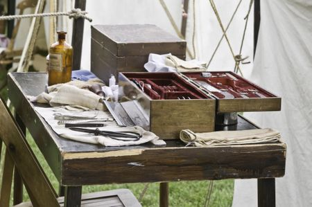 Instrument table in surgeons's tent, with bottle of chloroform and amputation saw, at reenactment of American Civil War (1861-1865), Lombard, Illinois (foreground focus)