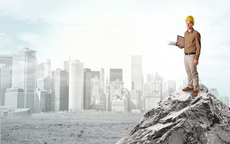 Young architect looking to ruined city from distance and thinking about investments